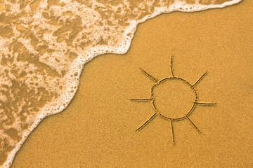 Sun drawn in the sand of a beach.