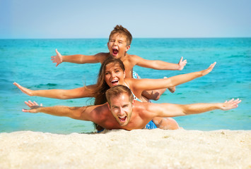 Wall Mural - Happy Young Family with Little Kid Having Fun at the Beach