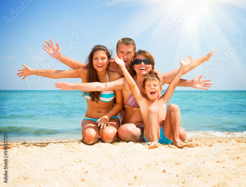 Wall mural Happy Family Having Fun at the Beach. Vacation concept