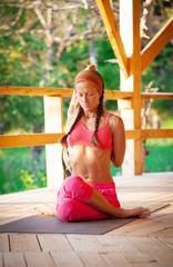 Slim flexible young girl doing yoga exercise