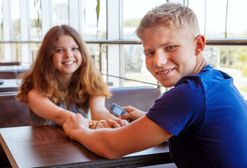 Attractive teenage couple sitting in cafe