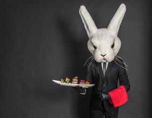 Rabbit waiter man in black suit stay at dark gray background