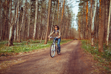 Young woman riding bicycle on a forest