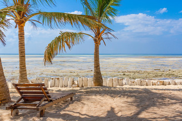 Chair and green trees on a white sand beach. Watamu, Kenya - Afr
