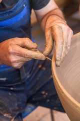 Potter works with clay in ceramics studio