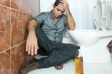 Drunk and depressed man sitting on the toilet floor