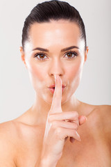 woman holding a finger in front of mouth as a sign of silence