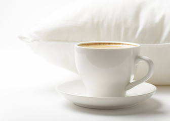 Cup of coffee and white pillow