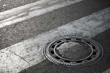 Sewer manhole cover on dark asphalt road