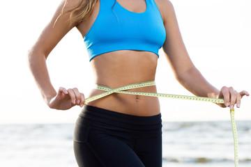 Fitness girl measures her waist