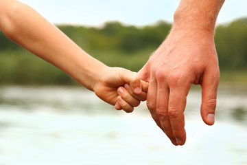 father's hand lead his child son against summer forest and river
