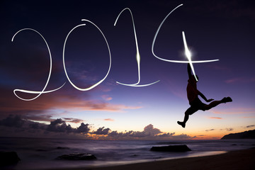 happy new year 2014.young man jumping and drawing 2014 by flashl