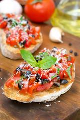 Italian bruschetta with tomato, olives, basil and cheese closeup