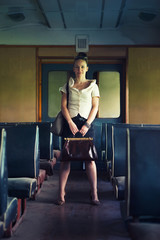 Woman with a suitcase walking in wagon of the retro train