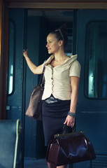 Woman with a suitcase in the retro train