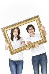Two young girls looking through the picture frame