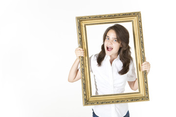 Teenager looking through picture frame making silly face