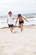 glückliche kinder spielen mit ihrem vater fußball am strand