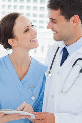 Smiling doctor and surgeon attractively looking at each other