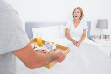 Husband bringing breakfast in bed to surprised wife