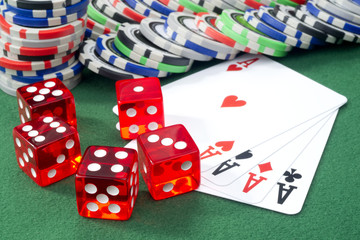 Red dice, four aces and chips on a green felt