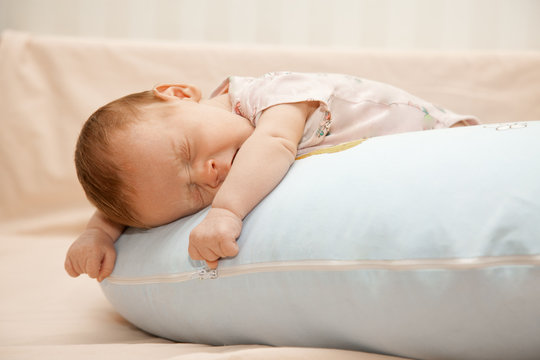 Newborn baby laying on his tummy on the pillow