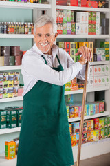 Senior Male Owner Standing Against Shelves In Supermarket