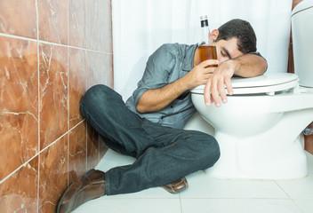 Drunk hispanic man sleeping over the toilet bowl