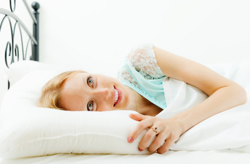 Blonde woman awaking in her bed at home