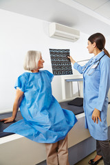 Ärztin schaut auf Röntgenbilder neben Seniorin