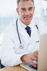 Smiling experienced doctor typing on his laptop