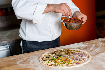 Cropped image of a chef preparing pizza