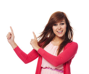 Beautiful woman in pink pointing at copy space