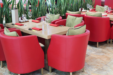 Tables with glasses, soft red armchairs