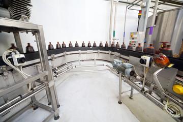Brown plastic bottles with fresh beer go on conveyor belt