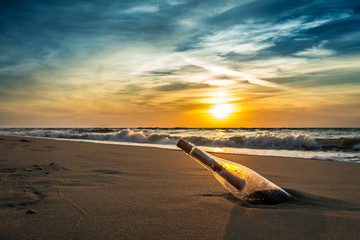 Message in a bottle on a beach against the setting sun