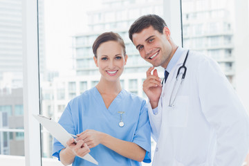 Cheerful surgeon and doctor posing while working together