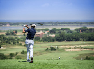 A male golfer finishes his swing