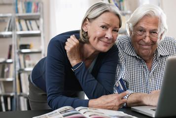 Deutschland, Wakendorf, erwachsene Frau mit Kreditkarte und Mann mit Laptop