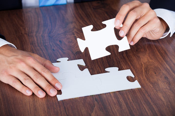 Close-up Of Businessman Completing Jigsaw Puzzle