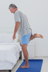 Mature man stretching his leg on an aerobic mat