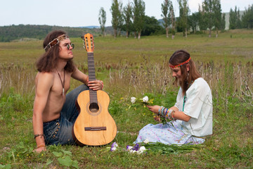 young hippie men with guitar and woman