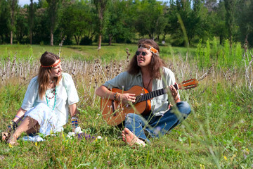 young hippie men play on the guitar