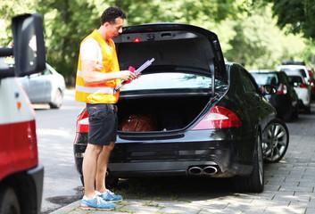 Mann holt Warndreieck aus Kofferraum