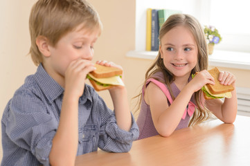 Children eating sandwiches. Two cheerful children eating sandwic