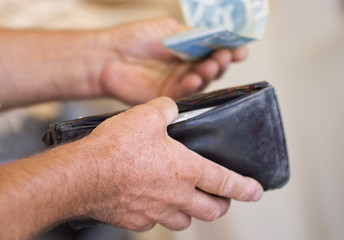 Man pulls money from his wallet to pay