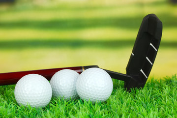 Golf balls and driver on green grass outdoor close up