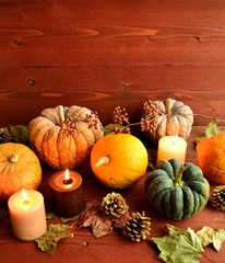 Pumpkins with candles on brown wood background
