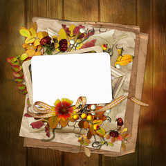 Frame with autumn leaves and berries on wooden background