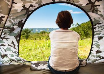 Girl sitting near open tourist tent door